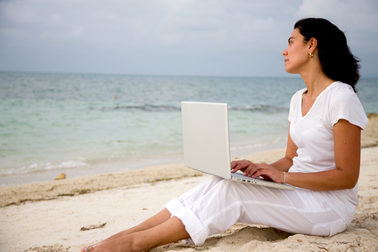 Woman working on a computer at the beach